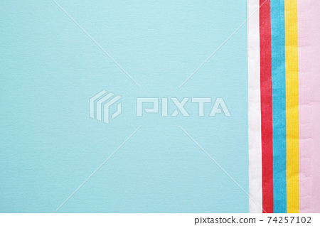 Colorful flower paper and a large copy space that overlaps the right edge of blue drawing paper 74257102