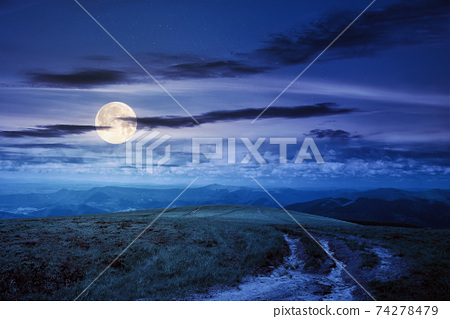 path through green grassy mountain meadow at night. beautiful summer landscape in full moon light. fine weather with fluffy clouds on the blue sky 74278479