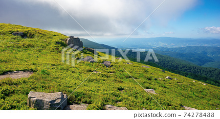 mountain meadow on a sunny morning. cloud rolling above the hill with rocks among the grass. warm summer weather. beauty of carpathian landscape in green and blue 74278488