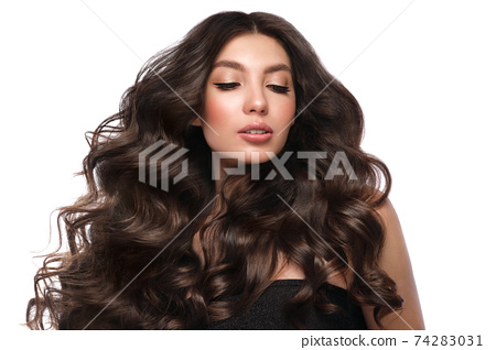 Beautiful brown-haired girl with a perfectly curls hair, and classic make-up. Beauty face and hair. 74283031