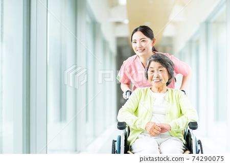 휠체어 수석 여자와 간호하는 젊은 여성 74290075