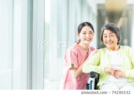Senior woman in wheelchair and nursing staff 74290332