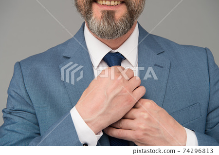 Attention to details. Male hands tie necktie grey background 74296813