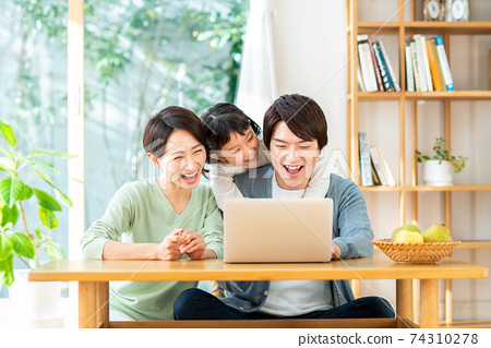 A young family watching a computer 74310278