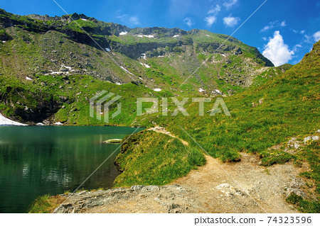 balea lake in fagaras mountain of romania. beautiful landscape in summertime. rocky slopes with grass in snow. sunny weather with fluffy clouds on the sky. popular travel destination 74323596