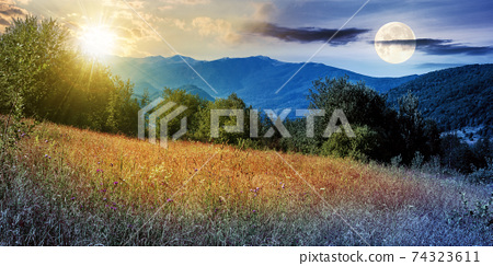 day and night time change concept above rural field in mountains. beautiful summer landscape of carpathian countryside with sun and mooon. trees on the hill, forested ridge in the distance beneath a 74323611