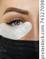 Eyelash Extension Procedure. Beautiful Woman with Extreme Long False Eyelashes. Makeup, Cosmetics. Beauty, Skincare. Woman in medical mask. 74327098