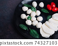 White small mozzarella cheese balls, spinach leaves and tomatoes on black plate. 74327103