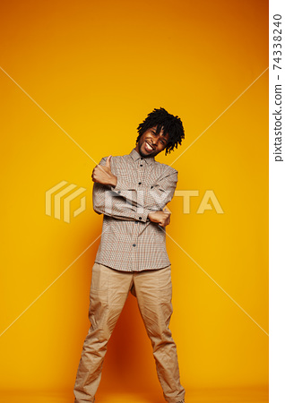 young handsome african american guy student posing cheerful and gesturing on yellow background, lifestyle people concept 74338240