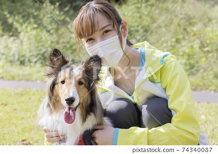 面具和她的狗排隊的年輕女子 74340087