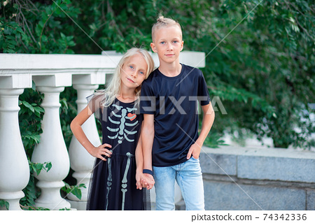 Modern children. Brother and sister in black robes stand by the handle. Skeleton pattern on dress 74342336