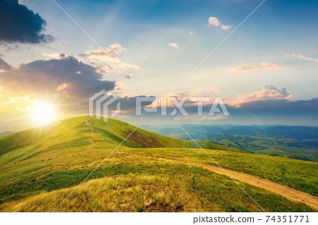 mountain landscape on a bright spring sunset. path through meadow in grass on the hill in evening light. wonderful weather with fluffy clouds on the sky. borzhava ridge of carpathians 74351771