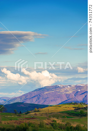mountainous rural landscape in springtime. beautiful scenery beneath a sky with clouds. grass covered hill rolling in to the distant ridge 74351772
