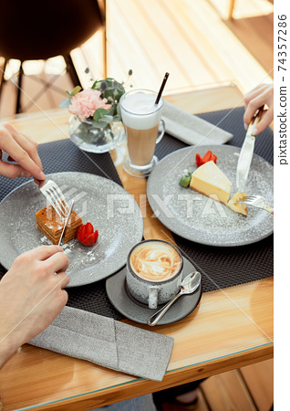 Young couple in a cafe eating coffee and dessert. Close-up of hands and bowl with dessert. 74357286