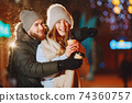 Young couple outdoor in night street at christmas time 74360757