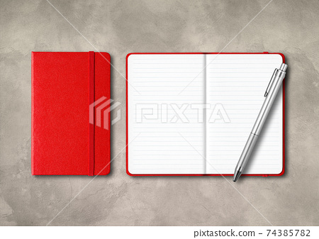 Red closed and open lined notebooks with a pen on concrete background 74385782