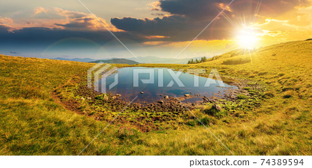 pond on the mountain meadow at sunset. wonderful summer landscape in evening light. grass and trees on the hills. ridge in the distance. beautiful wide panorama 74389594