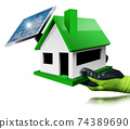 Gloved Hand Holding a Small Model House with Solar Panel on the Rooftop 74389690