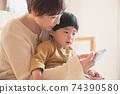 在家看一個男孩和智能手機的年輕母親 74390580
