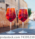 Two glasses of Spritz Veneziano cocktail served near the Venetian canal. 74395230