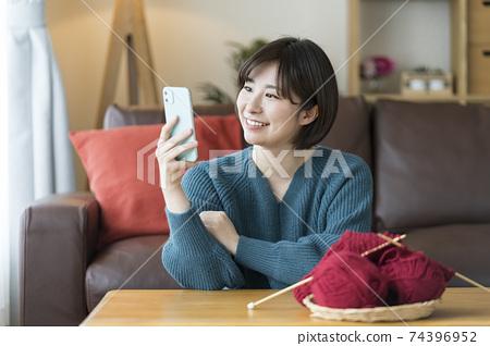 看著智能手機屏幕的年輕女子 74396952