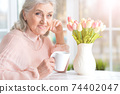 Portrait of beautiful smiling senior woman drinking tea 74402047