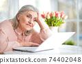 Portrait of happy senior woman using laptop 74402048