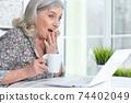 Close up portrait of happy senior woman using laptop 74402049