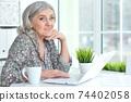 Beautiful senior woman using laptop at home 74402058