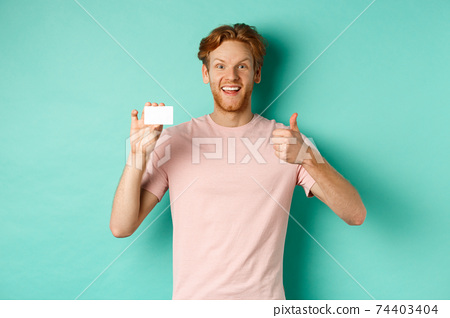 Cheerful male bank client in t-shirt showing thumb up and plastic credit card, smiling satisfied at camera, standing over turquoise background 74403404