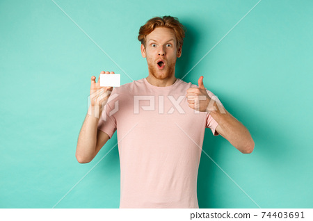 Adult guy with red hair and beard showing plastic credit card and thumb up, looking impressed, recommend bank, standing over mint background 74403691