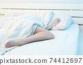 Lifestyle photo of girl under the covers on bed 74412697
