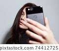 beautiful young woman posing for selfie 74412725