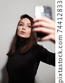 beautiful young woman doing selfie for social network 74412833