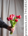 Man holding red tulip bouquet in front of a window curtain at home 74416932