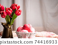 Red tulips and painted Easter eggs in front of a window curtain at home 74416933