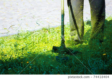 cutting lush green grass in the park. beautiful nature background. lawn care work in progress concept. brush cutter tool used to maintain gardens and outdoors 74418404