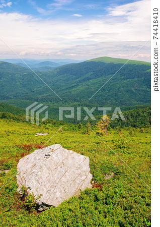 carpathian summer mountain landscape. beautiful countryside with rock on the grassy hill. view in to the distant valley. clouds on the blue sky 74418410