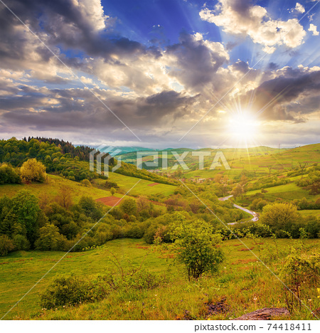 carpathian countryside in spring at sunset. beautiful rural landscape in mountain. wet grassy meadow in evening light. road winding through valley to village. distant ridge in the clouds 74418411