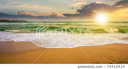 sea tide on a cloudy sunrise. green waves crashing golden sandy beach in morning light. storm weather approaching. summer holiday concept 74418414