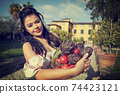 woman in white dress harvesting some fresh red cherry tomatoes in her own garden. concept of organic, ecological and biological farming and sustainability,green planet,connection with nature. Italy 74423121
