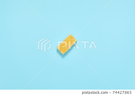 orange jelly slices in sugar on blue background. 74427863