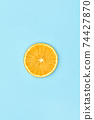 ripe slice orange fruit on blue background 74427870