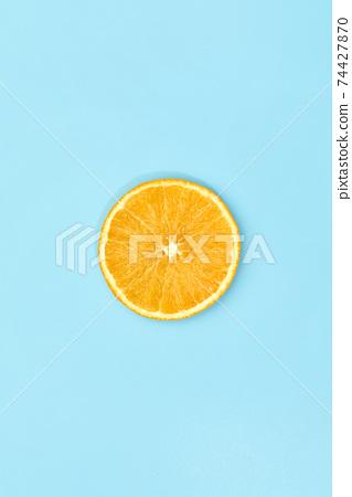 ripe slice orange fruit on blue background 74427870