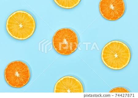 ripe slice orange fruit on blue background 74427871