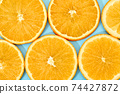 ripe slice orange fruit on blue background 74427872