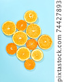 ripe slice orange fruit on blue background 74427893