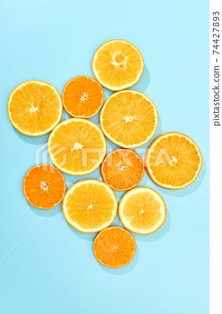 ripe slice orange fruit on blue background 74427893