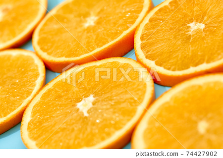 ripe slice orange fruit on blue background 74427902