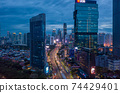 Aerial view of multi lane highway through modern city center with tall skyscrapers in blue evening light Night time traffic through downtown Jakarta, Indonesia 74429401